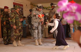 FOB MAHMUDIYAH, Iraq – Lt. Col. Kunk, 1st Battalion, 502nd Infantry Regiment, 101st Airborne Division, receives a gift from a student at Al Buhaira Elementary School. U.S. and Iraqi military officials visited the school as part of a ceremony celebrating the completion of a two-month long reconstruction project. (U.S. Army photo by Spc. Karl Johnson, 363rd MPAD)