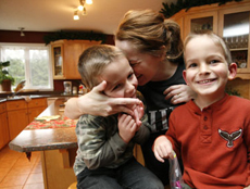 Noralee Harper hugs her son Brett as his twin brother Brendon looks on in Kildare Capes, PEI, last month. Brett was diagnosed two years ago at age four with non-Hodgkin's lymphoma, but is now doing fine.