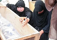 Women grieve beside coffins containing the remains of people executed by the Iraqi security forces in 1999, Basra.