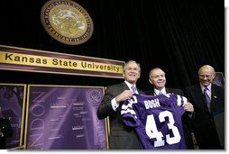 President George W. Bush receives a Kansas State Football jersey from University President Jon Wefald, center, with Kansas Senator Pat Roberts before delivering remarks on the global War on Terror at Kansas State University in Manhattan, Kan., Monday, Jan. 23, 2006. White House photo by Eric Draper