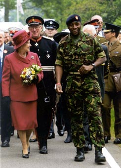 Photograph of the Lord-Lieutenant walking with the Queen and military cadets