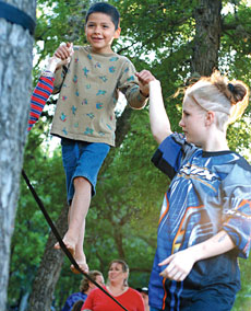 Brandon Hernandez walks a tightrope with the help of Destne Zieschang at Eeyore´s Birthday Party in Pease Park on Saturday afternoon. The event featured such activities as drum circles, egg toss competitions and other games for both children and adults.