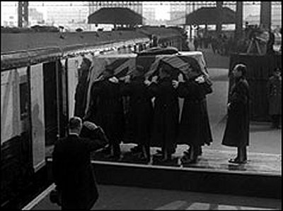 The bearer party places the coffin on the funeral train (PA)