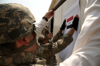Army Staff Sgt. Brendan Piper hangs a sign on the new Iraqi Assistance Center in Baghdad's Sadr City district on Sept. 2. Piper serves as the Iraqi Assistance Center noncommissioned officer in charge.