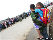 A mother carries her daughter with a new donated schoolbag at a relief centre in 21 May 2008 in Deyang, Sichuan province