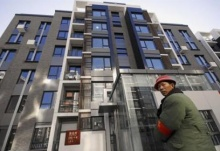 A man stands in front of a newly-built block of apartments in the Olympic Village in Beijing, January 23, 2008. REUTERS/China Daily