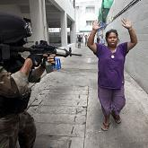 """An anti-government """"red shirt"""" supporter surrenders to army soldiers clearing an encampment of thousands of protesters in Bangkok"""