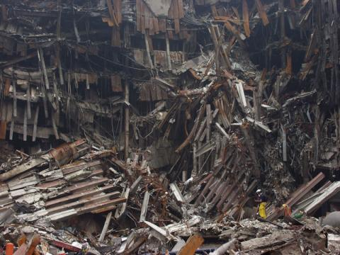 These rescue workers are dwarfed by the enormous pile of rubble at the site of the World Trade Center.