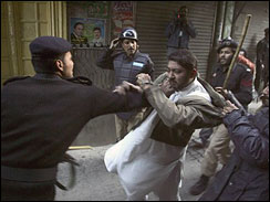 Pakistani police officers beat a protester as they detain him during clashes in Rawalpindi, Pakistan on Saturday, Dec. 29, 2007. Mass rioting following the assassination of opposition leader Benazir Bhutto has led to the deaths of 38 people and caused tens of millions of dollars in damage, the government said.