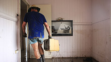 Volunteer moves TV from flooded home