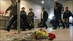 Passengers at Domodedovo airport walk past flowers laid out for victims of Monday's blast