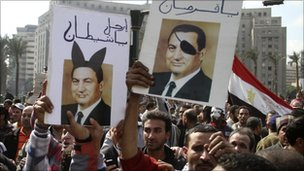 Protesters in Cairo, Egypt, hold defaced images of President Hosni Mubarak - 30 January 2011