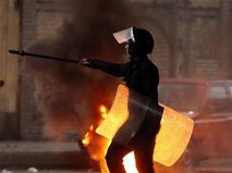 A riot policeman walks past burning tyres placed to form a barricade during clashes with protesters in Cairo