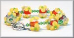 This bracelet is made of approximately 13 x 15mm Lampworked Glass beads. They are a clear bead with a Burnt Orange center and pale creamy Yellow Flowers added to the outside of the clear glass bead. The Yellow Flowers have a peridot green center accent. This bracelet is also accented with peridot green Swarovski Crystals and Sterling Silver Daisy Bali spacers. The 13mm Heart shaped Toggle Clasp is Sterling Silver as well.
