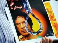 A Libyan protestor carries a placard during a protest rally against Libyan leader Col Gaddafi in Kuala Lumpur, Malaysia, on 23 February 2011