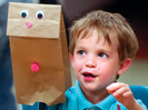A boy smiles after finishing his hand puppet during a puppet making workshop at the Byram Archibald Neighborhood Center, in Greenwich, Conn., Tuesday, May 15, 2007.