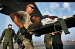 A wounded earthquake survivor is loaded into a U.S. Air Force C-130 cargo plane bound