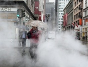 Rain and steam from a man hole cover envelope walkers in downtown San Francisco