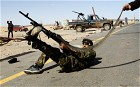 A rebel fighter fires his rifle at a military aircraft loyal to Libyan leader Muammar Gaddafi at a checkpoint in Ras Lanuf