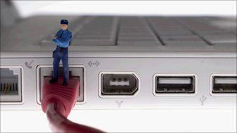 Figurine of a security guard standing on computer cable