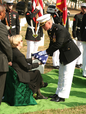 Col. W. Blake Crowe, commanding officer of Marine Barracks Washington, presents Valerie Bale, niece of Pfc. Carl A. West a fold flag, during West's interment with full military honors at Arlington National Cemetery, Oct. 4.   The Department of Defense Prisoner Of War/Missing Personnel Office announced recently that the Marine?s remains had finally been found and identified after being labeled as Missing in Action for more than 57 years.   Photo by: Gunnery Sgt. Will Price