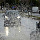 Varios vehículos cruzan una balsa de agua formada en una calle de Pamplona tras la fuerte tormenta de lluvia y truenos que ha caído esta tarde en la capital navarra.