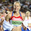 Tatyana Chernova of Russia celebrates with her country's flag after claiming gold in the women's heptathlon during day four