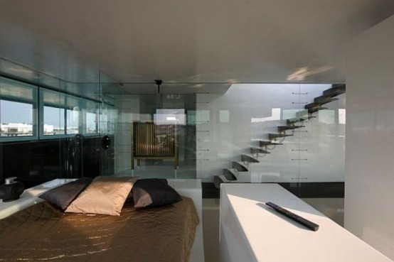 Bedroom at Modern Penthouse Interior With Lot of Glass Windows and Door