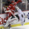 Detroit Red Wings left wing Drew Millercollides with Minnesota Wild goalie Josh Hardingduring the third period of an NHL hockey game in Detroit, Tuesday, Nov. 1, 2011. Miller was penalized for charging. (AP Photo/Carlos Osorio)
