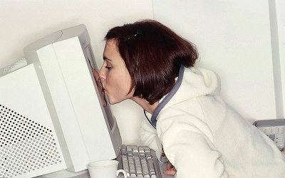 Woman kissing her computer
