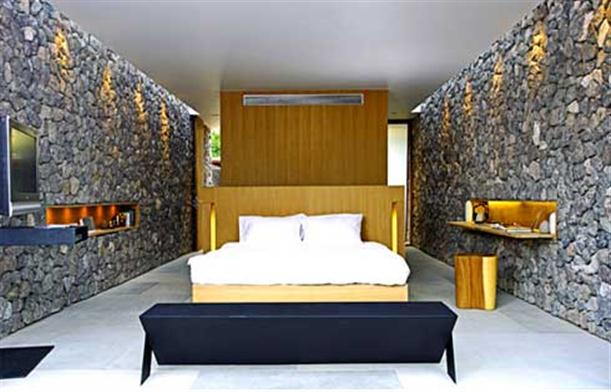 Front view of bedroom with unique stone wall at X2 Resort Kui Buri]