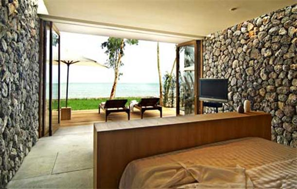 Outside beach looks from bedroom with unique stone wall at X2 Resort Kui Buri