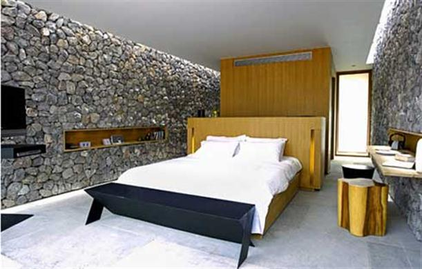 The bedroom interior with unique stone wall at X2 Resort Kui Buri