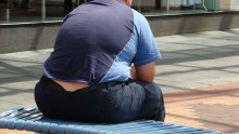 Obese man sits on a bench