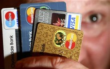 a man holds up some credit and debit cards. UK to raise extra £200m from bond sales, says Debt Management Office