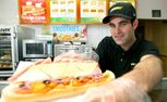 Subway store co-owner Ashley Knight holds up the ham sub he whipped up at the Blanchard St store yesterday. Ashley is off to Florida for his shot at the Subway world crown.