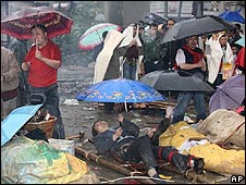 Injured earthquake victims lie in the rain in Beichuan county, China
