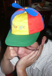 """Asian man in his twenties wearing a blue, green, yellow and red propellor hat that says """"Noogle"""""""