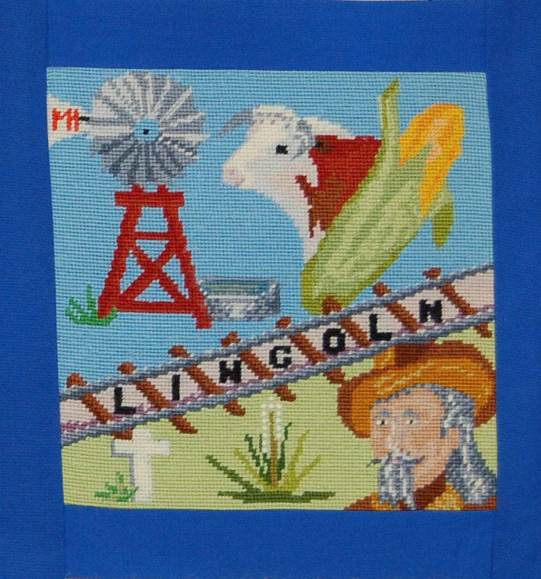 """From the accompanying booklet:  """"Many aspect of life in Lincoln County are represented in its needlepoint square.   Windmills, irrigation wells and canals provide water for crops and cattle. Ranching and farming operations are symbolized by corn, yucca, the cow and by the design's green background.  The Union Pacific Railroad operates one of the largest industries in the county, North Platte's Bailey Yards.  Buffalo Bill Cody's home at Scout's Rest Ranch is visited by people from all over the world each year.  A white cross depicts Fort McPherson National Cemetery, located south of Maxwell.""""  The block was designed by the Fantastic Fraulines Extension Club, the Medicine Creek Lassies Extension Club and Mrs. James C. Martin.  The needlework was done by Mrs. Robert Hendrickson."""