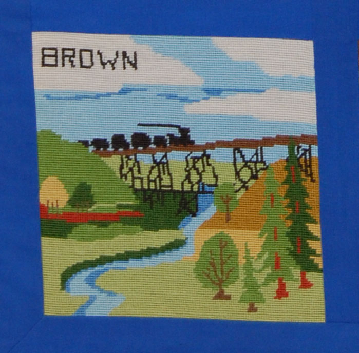 """From the accompanying booklet:  """"Brown County, in north central Nebraska, is represented by a landmark familiar to Brown County residents.  The railroad trestle southwest of Long Pine was built in 1905 and is one of the tallest in the state.  It is an integral part of the county's history and remains in use today.  Pine Creek, well known for its fish, wildlife and recreation, flows under the trestle.  Blue sky and fluffy white clouds typify not only Brown County, but the entire state.""""  The block was designed by the Lamplighters Extension Club and the needlework was done by Mrs. Art Fernau, Mrs. Duane Philben, Mrs. Henry Voss, and Mrs. Roy Preston."""