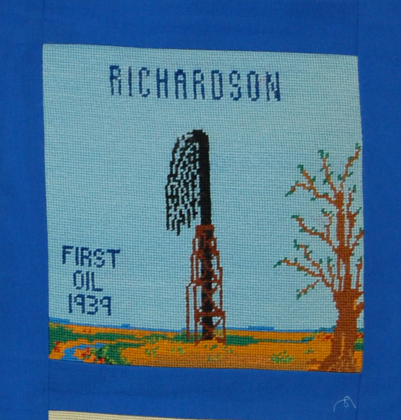 """From the accompanying booklet: """"Throughout the history of Richardson County many industries have been built through the efforts of its citizens.  Pioneers were the first to make use of the land for growing crops and feedling livestock.  Nebraska's first producing oil well was drilled in Richardson County in 1939.  Since then more oil wells have been drilled.""""  The block was designed by Tim Kean and the needlepoint was done by Mrs. Friel Kerns, Jr."""