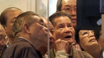 Elderly investers crowd around a share price monitor at a brokerage in Hong Kong
