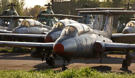 Varios L-29 en primer plano con helicópteros Mi-2 de fondo