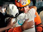 Image: A rescuer consoles a victim's relative