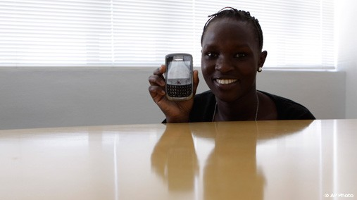 In this photo taken, Nov. 8, 2011, a woman poses with her Blackberry mobile phone in Johannesburg. The woman says she cherishes her phone as a link to family and friends, and also sees it as a radio, a library, a mini cinema, a bank teller, and more. [AP File Photo]
