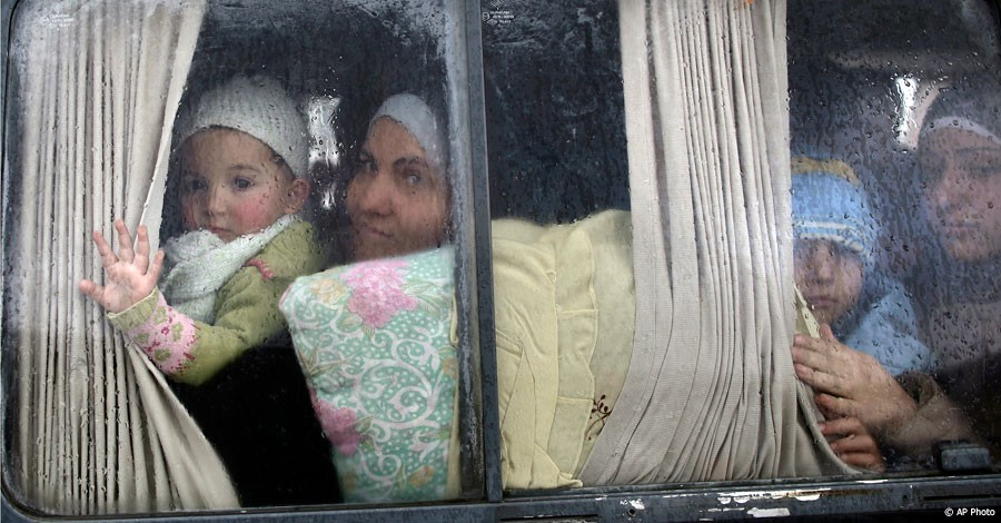 Syrian refugees look out of a vehicle's window just after crossing the border from Syria to Turkey, in Cilvegozu, Turkey, December 20, 2012. [AP Photo]