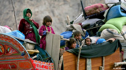 Afghan refugee children stand on their belonging loaded on a truck as they depart for Afghanistan at a UNHCR repatriation terminal near Quetta, Pakistan, Nov. 17, 2012. [AP File Photo]