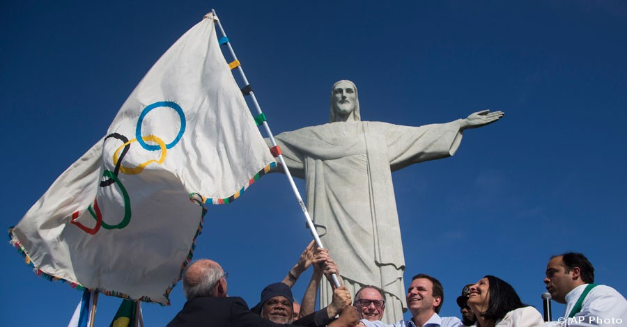 Rio de Janeiro's Mayor Eduardo Paes, third right, Brazilian Olympic Committee president Carlos Arthur Nuzman, center, and representatives from civil society wave the newly arrived Olympic flag in front of the Christ the Redeemer in Rio de Janeiro, Aug. 19, 2012. In 2016, Rio de Janeiro will host the Olympic Games. [AP File Photo]