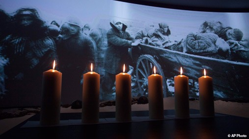 Memorial candles are lit in front of a photo taken during WWII showing refugees fleeing from the Nazis at a ceremony marking International Holocaust Remembrance Day in Russia's first Jewish Museum in Moscow, Russia, Jan. 27, 2013. [AP Photo]