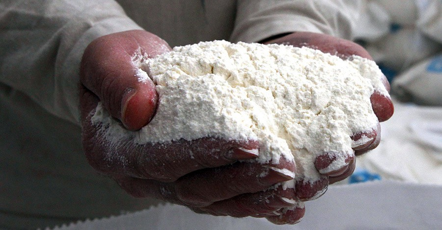 A flour mill employee holds freshly milled flour for Syrian bakeries, Aleppo, Syria, March 1, 2013. [USAID photo/ Used by Permission]